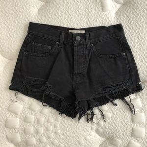 Free People black denim shorts with a lace detail.
